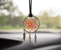 This cute dream catcher is made of a steel circle (which you can find at home on curtains), a yarn for the loops, and some feather pendants in case you haven't found real ones. It gives the look of a modern dream catcher.