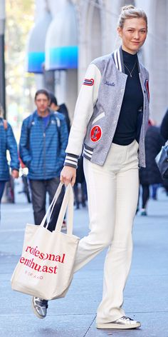 Karlie Kloss served up another one of her excellent model off-duty looks, in which she gave her black ATM turtleneck and white wide-leg pants a hit of street-chic appeal with a Karlie-embroidered Opening Ceremony varsity jacket and sneakers.