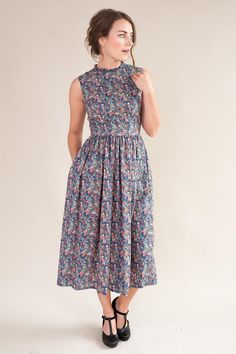 Sleeveless floral dress, handmade in a beautiful Liberty of London lightweight tana lawn fabric. The fitted bodice has a round neckline with ruffled detailing and is lined with a plain navy cotton fabric The midi length gathered skirt has in seam pockets and a concealed zip fastening
