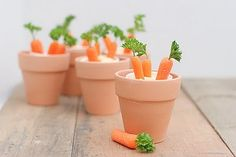 """Carrots dipped in hummus in small cups for """"dirt"""", terra cotta pots for decor."""