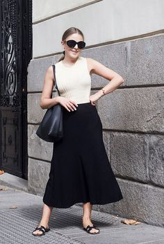 White ribbed tank top, a black a-line midi skirt, black slide sandals, black sunglasses and a black tote bag. #summerstyle #summerfashion #fashion2018 #midiskirt #fashiontrends2018 #ootd #outfitideas #minimalstyle Summer outfit, hot day outfit, midi skirt outfit, casual outfit, summer style, hot weather outfit, comfy outfit, black and white outfit, minimal outfit.