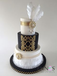 """I was so happy to finally have the chance to make a Great Gatsby cake, I so wanted to make an Art Deco cake and I finally did! This cake was so much fun to make, it's a three tier cake 8"""", 6"""" and 4"""". The bottom tier has wafer paper fringe, 50/50 pearls and brooch. For the middle tier I used the wax paper transfer technique, to get that clean and beautifull gold lines. I used a puncher and Wilton's edible paper painted in gold to make the lace on the top tier and the feathers are wafer paper."""