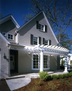 Add a pergola to face front and a house becomes house-art - Do like the scalloped patio pavers