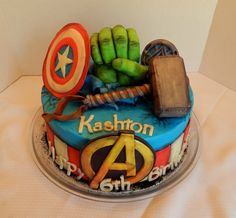 Kashton's Avengers cake! 12 inch round 2 layer cake with Hulk's hand bursting through the cake, Thor's hammer, Captain America's shield, Iron Man's chest piece and the Avenger's logo front and center!! All buttercream, candy clay and rice krispy treats! All edible, no fondant!! I think this is my new favorite cake!! lol https://www.facebook.com/angelas.cakes2011