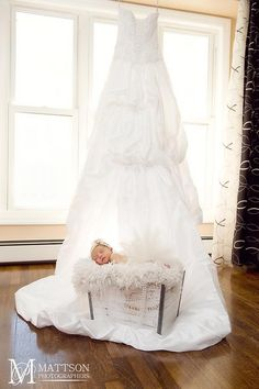 Baby girl with mom's wedding dress.