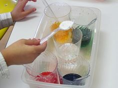 a drop of coloring in spoon of baking soda and then mixing into cup of vinegar for surprise color and bubbles. We did this and it was easy and fun - followed by pouring colors together to make new colors, so have some empty cups ready.