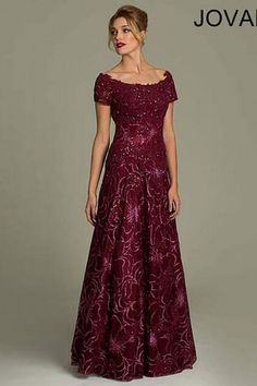 Off-the-shoulder wine colored A-line gown features a floral print, cap sleeves, beaded adornments and a hidden zipper in the back.