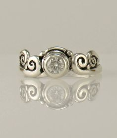 R1130- Sterling Silver Ring with a 4.5 mm Classic Moissanite. Size 7.25, I can size it to fit, just contact me. No charge to size down. Convo me on sizing up.   The top of the ring measures 8 mm and the band is 2 mm. All of my pieces are One of a Kind.  This ring is made by the Lost wax Casting method, where I make the design in wax and then cast it into silver. To learn more about Me and the Lost Wax Method please visit my website at www.denimanddiamondsjewelry.com  Thanks for visiting, If…
