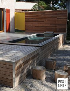 Piscinel Piscinelle hors-sol semi-enterrée avec terrasse bois réalisée en ipé et bardage esthétique en bois.