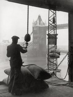 Pool of London Dockworker handling a cargo of bagged nuts by . Museum quality art prints with a selection of frame and size options, and canvases. Museum of London Uk History, London History, British History, Modern History, East End London, Old London, London Pride, London Docklands, London Boroughs