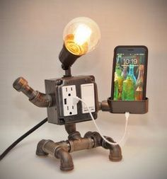 """This lamp is a cute yet very functional addition to any room. Perfect for your night stand, this lamp features two grounded AC outlets, two high-power USB charging ports, a Dimmer, and a smartphone charging cradle that can accommodate up to an iPhone 7 Plus (even with a case, as shown). Lightning cable (1-foot, as shown) is $15 extra, if needed. The main light is a 40-watt G25 """"squirrel cage"""" bulb, controlled by the Decora rocker switch with dimmer on the front. Can be replaced with any…"""