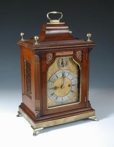 Sale F160915 Lot 639 A & H Rowley, London, a late Victorian mahogany bracket clock, the Georgian style case with inverted bell top and brass handle, four ball finials, foliate engraved gilt dial with strike/silent to the arch, silvered chapter ring signed below, twin fusee gong striking movement, fretwork side panels and glazed rear door, all on a brass plinth and bracket feet h:38 w:26 cm - Cheffins