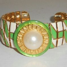 Couture CC button cuff bracelet Authentic stamped CC button from my personal collection, on green, gold and white enamel cuff bracelet. Slightly adjustable. Cuff is vintage but never worn. Button measures 1.25 inches across. Cuff measures 1.2 inches wide by 7.5 inches. CC button is mounted on a large lime green Dana Buchman mother of pearl coat button. Jewelry Bracelets