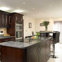 luxury contemporary kitchen dark wood cabinetry new caledonia granite countertop