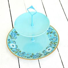 "Jardin Cake Stand - These complementary yet unique plates have been assembled into a stunning tabletop display. Assembles and disassembles easily for storage. Top tier: 6.5"" diameter. Bottom tier: 10.5"" diameter. Total height 10"". Hand-drilled. Hardware: enamelware. Made of repurposed vintage estate china dating back to the 1930s. ($48/$66 retail)"