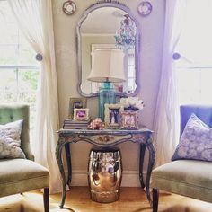Decorator Tip: Use symmetry in decorating to get a polished look. Flank a center table, mirror and lamp with a pair of chairs, a matching pair of pillows between a pair of windows. The balance of it all is the appeal. Fill out the table with photo frames, a vase of flowers and a few books. Last but not least we put a silver garden stool from Homegoods underneath an antique table because opposites attract! Sponsored by HomeGoods.