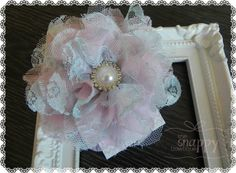 Reminiscent of a summer sunset, this beautiful blossom is soft and serene in gentle hues of light pink and blue and topped off with a brilliant pearl-rhinestone center. Gorgeous from The Snappy Bowtique!