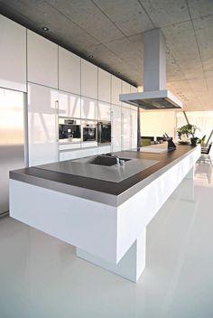 Die Decke aus Sichtbeton ist das absolute Highlight der Küche. Neben dem riesigen, weißen Küchenblock mit der grauen Arbeitsplatte und den Küchenschränken in Hochglanzoptik versprüht er lässigen Industrie-Charme.