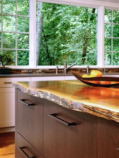 Designer Lauren Bland turns a cluttered, messy kitchen into a spacious, organized kitchen with white cabinets, a reclaimed wood island and a gas range. Check it out at HGTV.com
