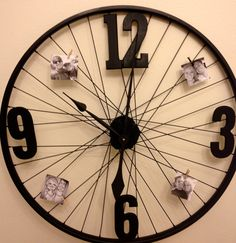 DIY Bicycle wheel clock. Spray paint wheel and numbers from Hobby Lobby. Hot Glue the numbers on, add a clock motor, and clothes pin little pictures all over it. ($19.99)