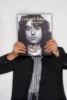 Jimmy Page holding up his autobiography Oct. 3, 2014 (book is due out Oct. 14, 2014)