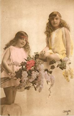 two girls in smocks, one sitting on wall, other kneeling to left with flowers