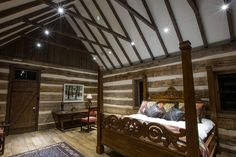 Master bedroom in ranch home. Custom made wooden bed frame. Cut aged-wood beams hang from the walls.