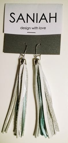 Hapsu earring with white leather and turquoise satin ribbons. Made of industrial surplus and recycled materials.