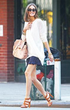 Olivia Palermo wears a white drapey sweater with a polka dot skirt, heeled gladiator sandals, a pink bag, and layered jewelry