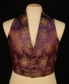 GENT'S PURPLE SILK BROCADE VEST, 1860's. Belonged to Peleg Bradford, 7th descendant of Governor Bradford of the Massachusetts Bay Colony. Green, yellow and gold floral clusters, shawl collar, two hem pockets, five self buttons, straight bottom, back lacing adjustment, (laces missing), backed and lined in tan cotton, hem reinforced in front with leather. Chest 40, length 19. Excellent. $517.50.
