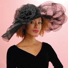 Off Face Floppy Black is a dressy derby hat by Louise Green. The large brim hat has a parisisal crown and a fancy sinamay brim with a large silk cabbage rose on the side.