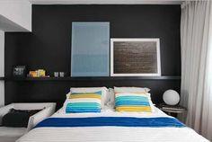 A parede da cabeceira da cama do apartamento dos publicitários Ângela e Marcone ganhou a cor preta com um suporte de madeira para apoiar e destacar os quadros do casal.