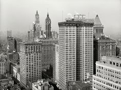 "New York circa 1917. ""Skyscrapers, looking north toward towers of Woolworth and Singer buildings."" Double-barreled tower in the foreground is the Adams Express Building."