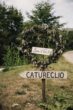 Greenery Wreathe Wedding Sign - Samuel Docker photography | Outdoor Italian Destination Wedding | Villa Catureglio Tuscany | Customised David Fielden Wedding Dress | Grey ASOS Bridesmaid Dresses | Cad & The Dandy Suit | Greenery & White Flowers