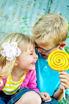 Little boy and girl laughing together as they share a lollipop.