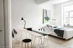 lautapöytä,valkoinen seinä,jakkara,taulu,yksiö,yksiön sisustus