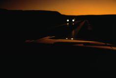 A car drives down a desert road in twilight, USA, September 1967.