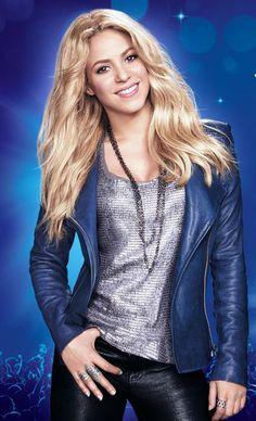 Shakira es de  Barranquilla, Colombia. Ella lleva una saco azul, una camisa plata, unos pantalones negras y una collar plata.