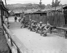 U.S. Marines crouch behind a railing during the Second Battle of Seoul on Sept. 27, 1950, as they  answer fire from some North Korean snipers left behind to try and  hamper the American advance into the South Korean capital.
