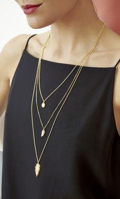 Three-tiered, delicate necklace with dainty charms in matte gold-toned metal.