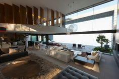 An open-concept great room with multiple seating areas and a balcony overlooking the space. Beneath the balcony is a more casual seating area, while near the folding glass shutters to the patio are two minimalist, more formal seating areas.