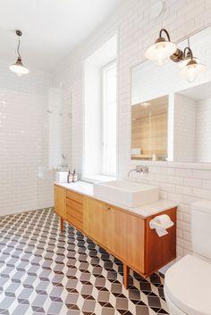 sol à effet 3D, armoire vintage et éclairage industriel dans la salle de bain rétro