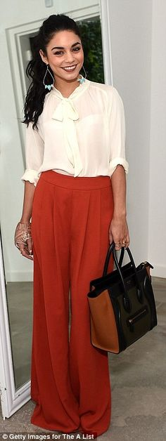 Seventies flare: She wore a white blouse tucked into a pair of bell-bottomed orange trouse...