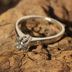 Rough diamond engagement ring with pave set grey diamonds on either side in sterling silver band
