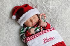 Baby in Christmas stocking with name embroidered on stocking, wearing Santa hat  clutching a candy cane.  From Sarah Jordan Photography.
