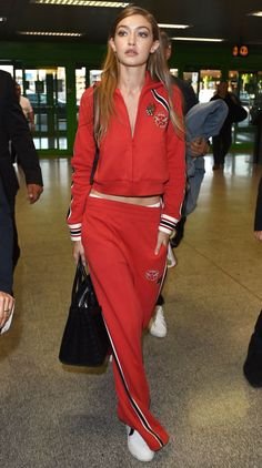 In a red Tommy Hilfiger tracksuit with white sneakers and a black tote bag on her way to a Tommy Hilfiger event in Milan.