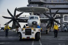 RED SEA (Nov. 30, 2016) Sailors maneuver an E2-C Hawkeye assigned to the Screwtops of Airborne Early Warning Squadron (VAW) 123 across the flight deck of the aircraft carrier USS Dwight D. Eisenhower (CVN 69). The ship and its carrier strike group are deployed in support of Operation Inherent Resolve, maritime security operations and theater security cooperation efforts in the U.S. 5th Fleet area of operations. (U.S. Navy photo by Petty Officer 3rd Class Nathan T. Beard/Released)