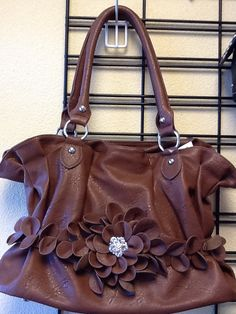 Basic Purse in Brown with Flower Embellishment: $49.99. Styles and colors not guaranteed. This item is currently at our Granite Bay Location. Call or Email for more information. Email: polkadotsproshop@gmail.com Phone: 916-791-9070