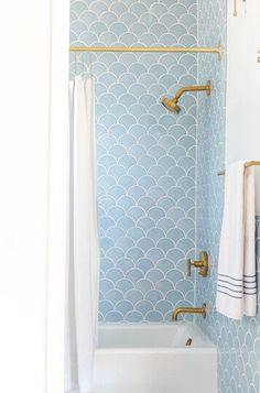 Brass shower head in bathroom with blue wall tiling