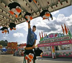 """Jason Kunst hangs up some stuffed animals at the """"water race"""" game on the midway which are prizes for contestants. Greg Derr/The Patriot Ledger"""